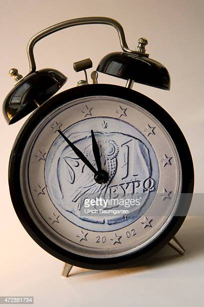 minutes before twelve for Greece and the Euro Symbol photo with alarm clock and a Greek 1 Euro coin as a clock face