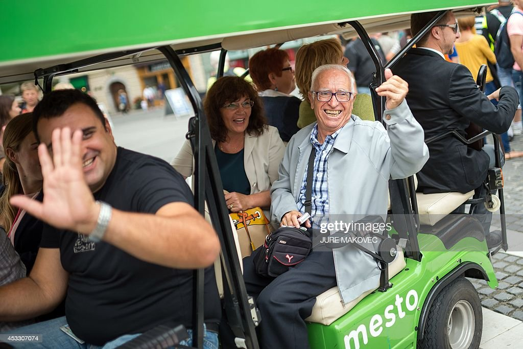 Miquel Ribas, an 82-year old Spaniard, waves as he visits Ljubljana on July 28, 2014, during a week-long trip to Slovenia. Ribas, who lives in a care home in Mataro, on the Spanish coast near Barcelona, has free accommodation during his trip in a similar care home in Topolsica, Slovenia, provided by Jozica Kucera, a 77-year-old Slovenian widow, who will spend the same time in his room in Spain. This is the first international exchange of rooms in care homes for seniors, organized by social networking agency Linkedage, a Slovenian company that developed a web platform to link residences all over Europe and the world to enable similar exchanges or to rent vacant rooms. AFP PHOTO / JURE MAKOVEC