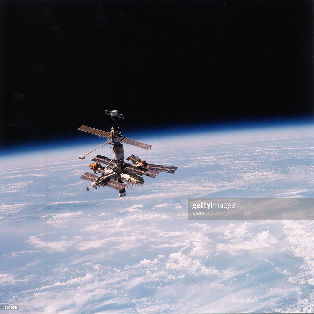Mir Space Station is backdropped over Earth's horizon as the Space Shuttle Atlantis performs its final fly around following undocking operations This...