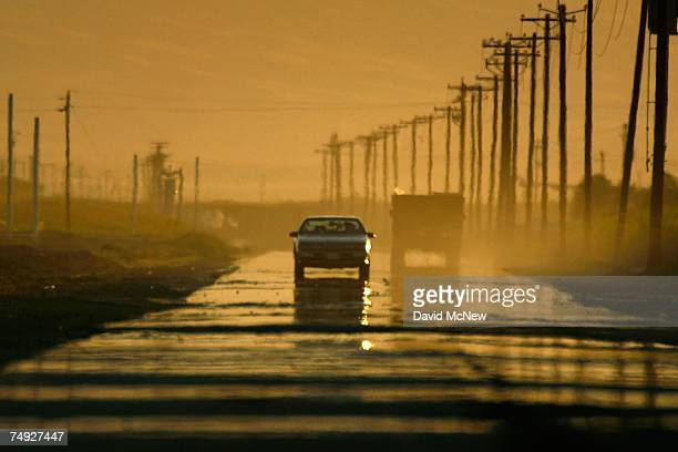 A mirage creates the illusion of water on a dry highway on a hot summer day as drought conditions worsen on June 25 2007 near Bakersfield California...