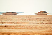 This place is popular in Sahara Desert, where you can see fata morgana, mirage - those hills in the distance are not real