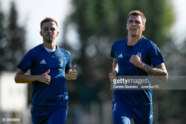 Miralem Pjanic and Mario Mandzukic of Juventus during a training session on July 13 2017 in Vinovo Italy