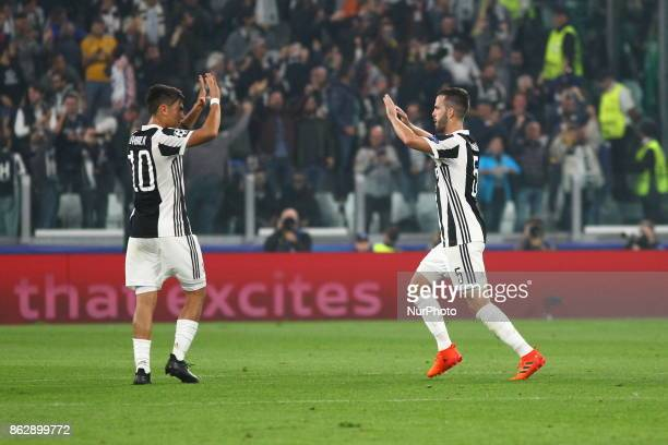 Miralem Pjanic celebrates after scoring with Paulo Dybala during the UEFA Champions League football match between Juventus FC and Sporting CP at...
