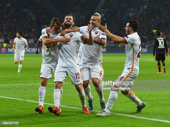 Miralem Pjanic of AS Roma celebrates as he scores their third goal with team mates during the UEFA Champions League Group E match between Bayer 04...