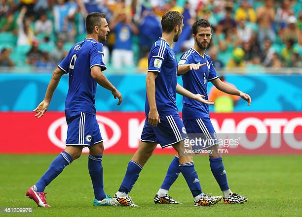Miralem Pjanic of Bosnia and Herzegovina celebrates scoring his team's second goal with his teammate Tino Sven Susic and Vedad Ibisevic during the...