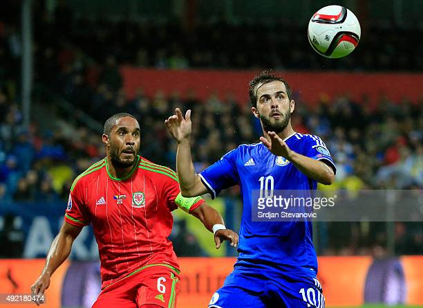 Miralem Pjanic of Bosnia in action against Ashley Williams of Wales during the Euro 2016 qualifying football match between Bosnia and Herzegovina and...