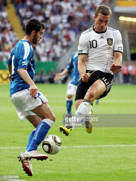 Miralem Pjanic of BosniaHerzegovina is challenged by Lukas Podolski of Germany during the international friendly match between Germany and...