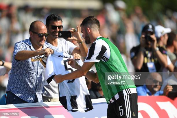 Miralem Pjanic of Juventus A signs autographs for fans during the preseason friendly match between Juventus A and Juventus B on August 17 2017 in...