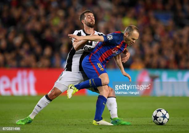 Miralem Pjanic of Juventus and Andres Iniesta of Barcelona battle for possession during the UEFA Champions League Quarter Final second leg match...