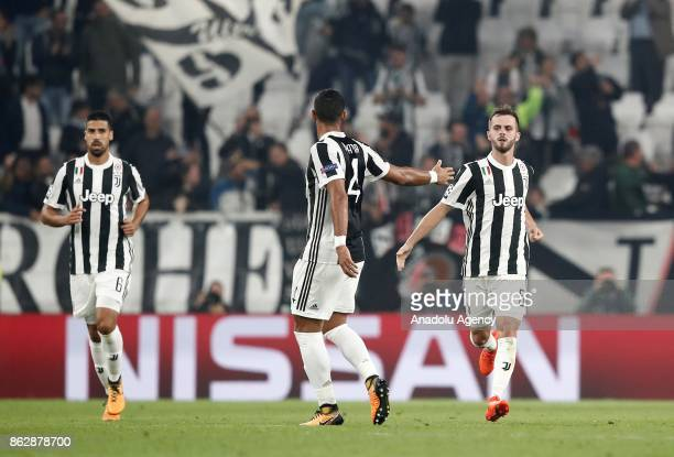 Miralem Pjanic of Juventus celebrates with his teammates Mehdi Benatia and Sami Khedira after scoring a goal during the UEFA Champions League group D...