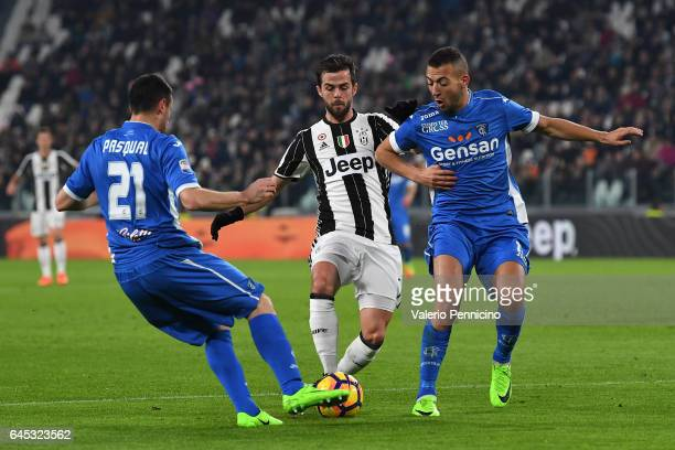 Miralem Pjanic of Juventus FC is challenged by Manuel Pasqual and Omar El Kaddouri of Empoli FC during the Serie A match between Juventus FC and...