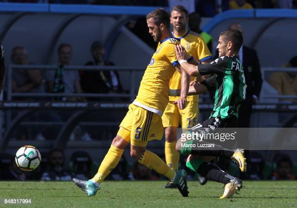 Miralem Pjanic of Juventus is challenged by Diego Falcinelli of US Sassuolo Calcio during the Serie A match between US Sassuolo and Juventus at Mapei...