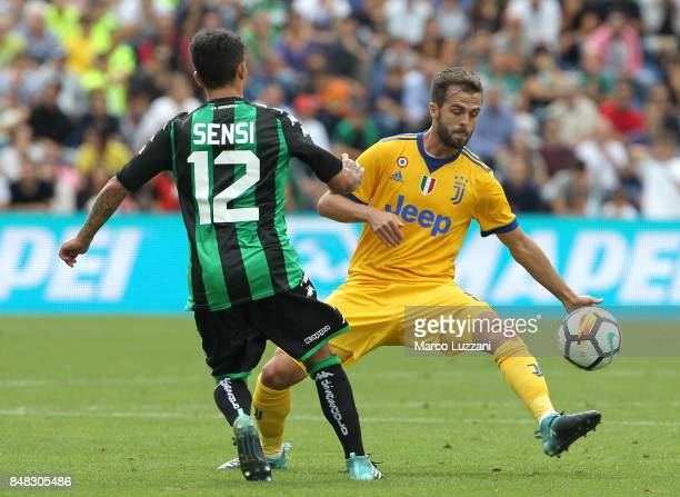 Miralem Pjanic of Juventus is challenged by Stefano Sensi of US Sassuolo Calcio during the Serie A match between US Sassuolo and Juventus at Mapei...