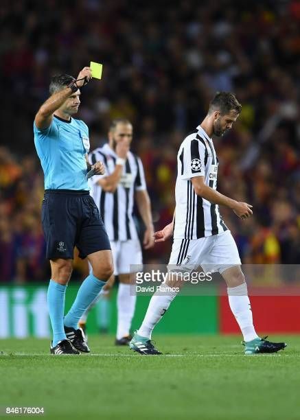 Miralem Pjanic of Juventus is shown a yellow card by referee Damir Skomina during the UEFA Champions League Group D match between FC Barcelona and...