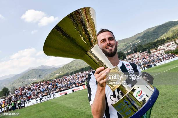 Miralem Pjanic of Juventus shows the Serie A trophy to the fans before the preseason friendly match between Juventus A and Juventus B on August 17...