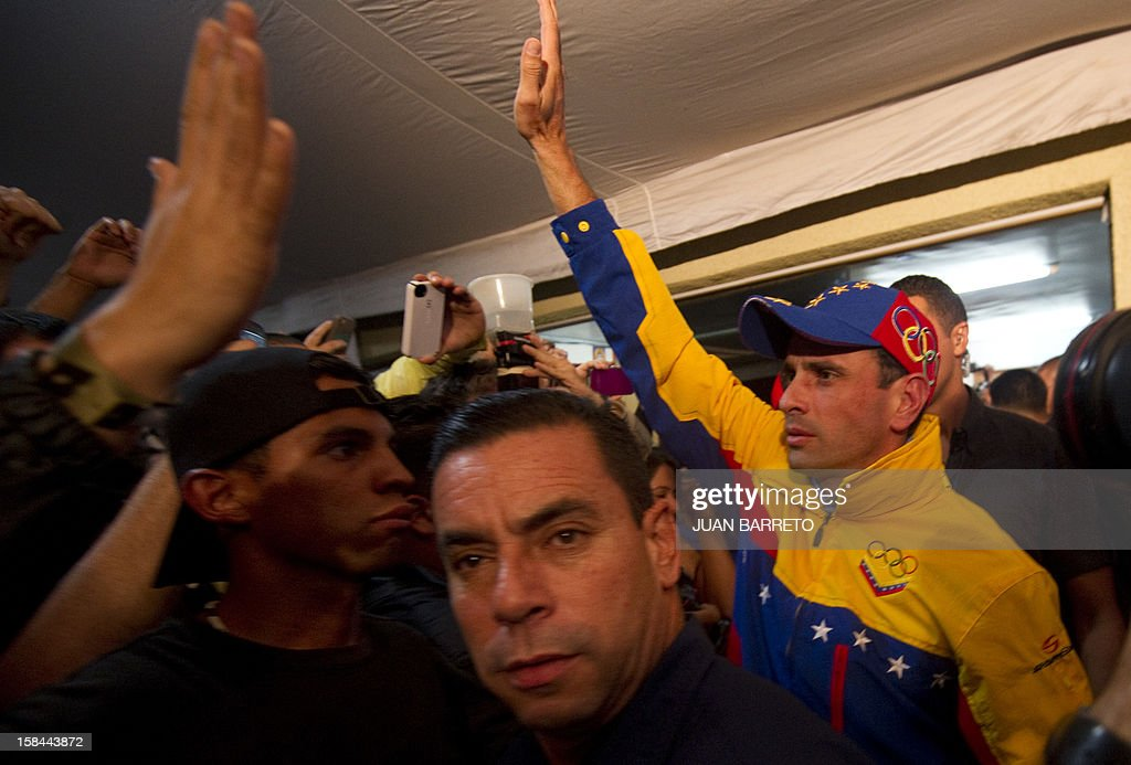 Miranda State governor and candidate for the re-election, Henrique Capriles Radonski (R), greets supporters after state elections on December 16, 2012. The candidate for reelection by the Democratic Unity Table (MUD) for governor of Miranda state, Henrique Capriles, won Sunday's regional election with 50.35% of the votes. AFP PHOTO