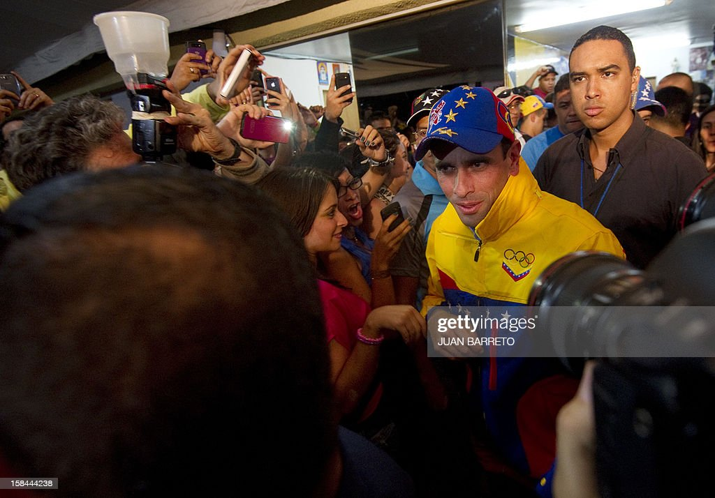 Miranda State governor and candidate for the re-election, Henrique Capriles Radonski (R), greets supporters after state elections on December 16, 2012. The candidate for reelection by the Democratic Unity Table (MUD) for governor of Miranda state, Henrique Capriles, won Sunday's regional election with 50.35% of the votes. AFP PHOTO/JUAN BARRETO