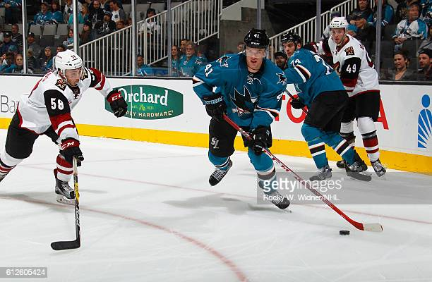 Mirco Mueller of the San Jose Sharks skates with the puck against Michael Bunting of the Arizona Coyotes at SAP Center on September 30 2016 in San...