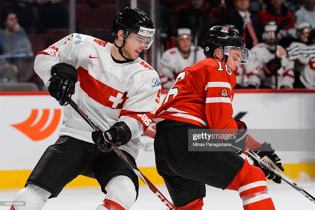 Mirco Muller #5 of Team Switzerland covers <a gi-track='captionPersonalityLinkClicked' href=/galleries/search?phrase=Max+Domi&family=editorial&specificpeople=8321782 ng-click='$event.stopPropagation()'>Max Domi</a> #16 of Team Canada during the 2015 IIHF World Junior Hockey Championship exhibition game at the Bell Centre on December 23, 2014 in Montreal, Quebec, Canada. Team Canada defeated Team Switzerland 6-0.