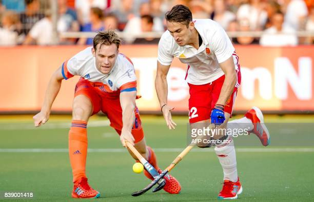 Mirco Pruyser from the Netherlands vies for the ball with David Condon from England during the men's hockey semifinal match Netherlands v England at...