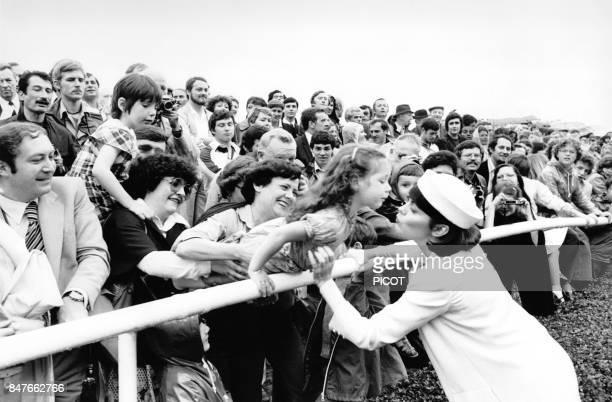 Mireille Mathieu en tenue claire et coiffee d'un chapeau embrasse une jeune admiratrice dans la foule en avril 1979 en France