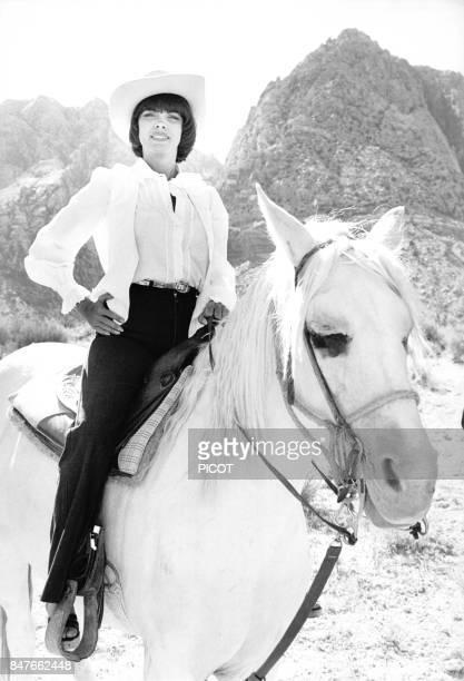 Mireille Mathieu fait une randonnee a cheval coiffee d'un chapeau de cowboy durant sa tournee americaine en juin 1978 aux EtatsUnis