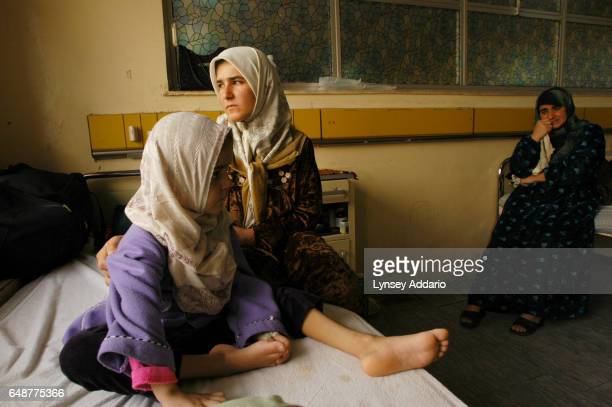 Miriam Hadi sits with her mother and aunt right in the Oncology ward of the Baghdad central pediatric hospital on February 12 in Baghdad Iraq Miriam...