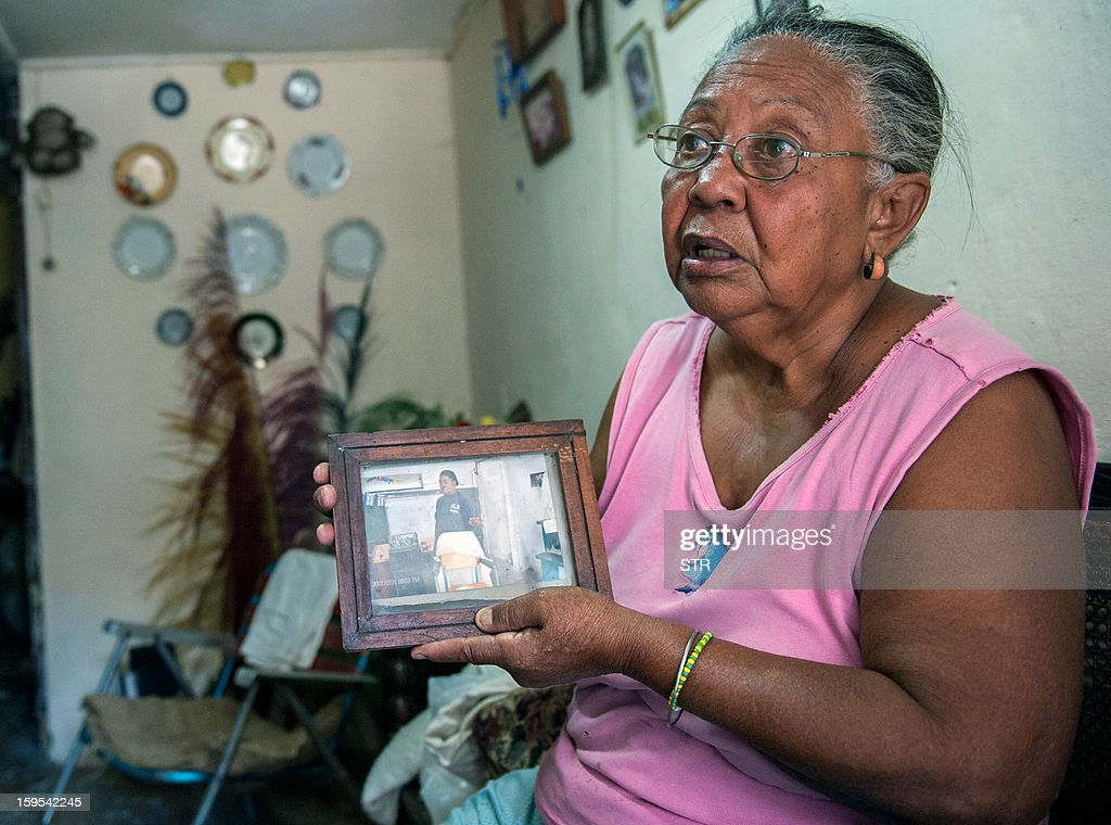 Miriam Rodriguez shows a picture of her late son Ubaldo Pino --who died of cholera last January 6-- on January 15, 2013 in Havana. The official newspaper Granma announced today a new cholera outbreak that has allegedly sickened 51 people in Havana.