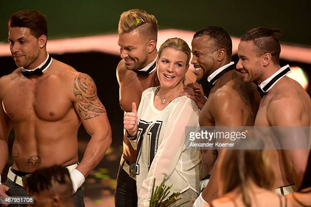 Mirja Boes stands between members of the Chippendales during the national tv show 'Willkommen bei Carmen Nebel' at TUI Arena on March 28 2015 in...