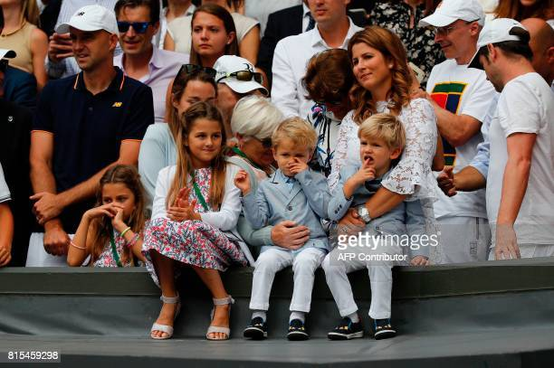 Mirka Federer wife of Switzerland's Roger Federer stands with her children Charlene Riva Myla Rose Lenny and Leo as her husband holds the winner's...