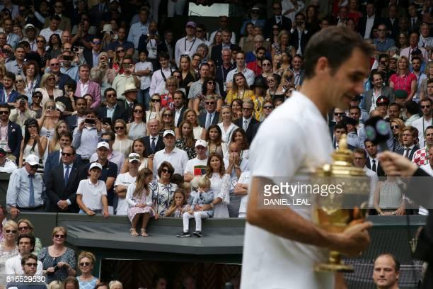 Mirka Federer wife of Switzerland's Roger Federer stands with their children Charlene Riva Myla Rose Lenny and Leo as her husband holds the winner's...