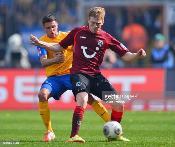 Mirko Boland of Braunschweig is challenged by Artjoms Rudnevs of Hannover during the Bundesliga match between Eintracht Braunschweig and Hannover 96...