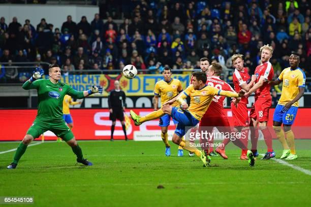 Mirko Boland of Braunschweig scores his team's first goal past goalkeeper Kevin Mueller of Heidenheim during the Second Bundesliga match between...