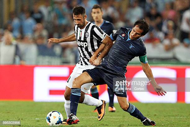 Mirko Vucinic of FC Juventus and Crisitna Ledesma of SS Lazio compete for the ball during the TIM Supercup match between SS Lazio and FC Juventus at...