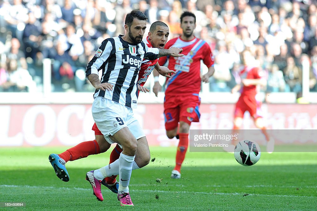 Mirko Vucinic (L) of FC Juventus is challenged by Giuseppe Bellusc of Calcio Catania during the Serie A match between FC Juventus and Calcio Catania at Juventus Arena on March 10, 2013 in Turin, Italy.