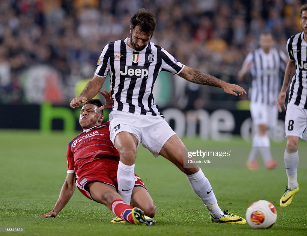 Mirko Vucinic of Juventus and Corentin Tolisso of Lyon (L) compete for the ball during the UEFA Europa League quarter final match between Juventus and Olympique Lyonnais at Juventus Arena on April 10, 2014 in Turin, Italy.