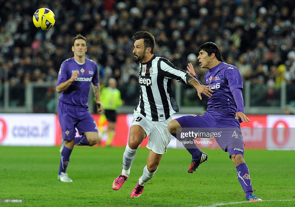 Mirko Vucinic (L) of Juventus FC is challenged by Facundo Roncaglia of ACF Fiorentina during the Serie A match between Juventus FC and ACF Fiorentina at Juventus Arena on February 9, 2013 in Turin, Italy.