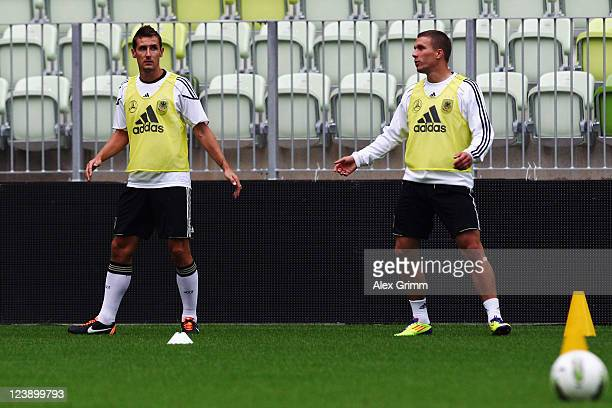 Miroslav Klose and Lukas Podolski exercise during a Germany training session ahead of their friendly match against Poland at Baltic Arena on...