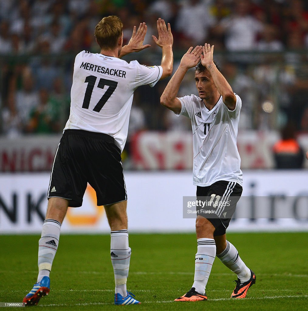 Miroslav Klose celebrates scoring his goal with Per Mertesacker of Germany during the FIFA 2014 world cup qualifier match between Germany and Austria at the Allianz Arena on September 6, 2013 in Munich, Germany.