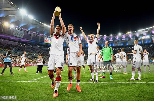 Miroslav Klose of Germany and Erik Durm of Germany lift the World Cup trophy to celebrate after the 2014 FIFA World Cup Brazil Final match between...