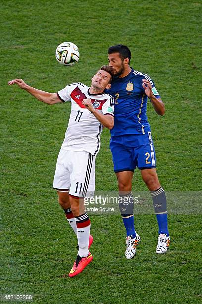 Miroslav Klose of Germany and Ezequiel Garay of Argentina go up for a header during the 2014 FIFA World Cup Brazil Final match between Germany and...