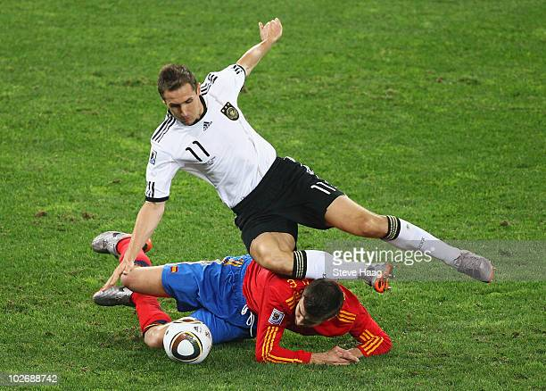 Miroslav Klose of Germany and Gerard Pique of Spain battle for the ball during the 2010 FIFA World Cup South Africa Semi Final match between Germany...