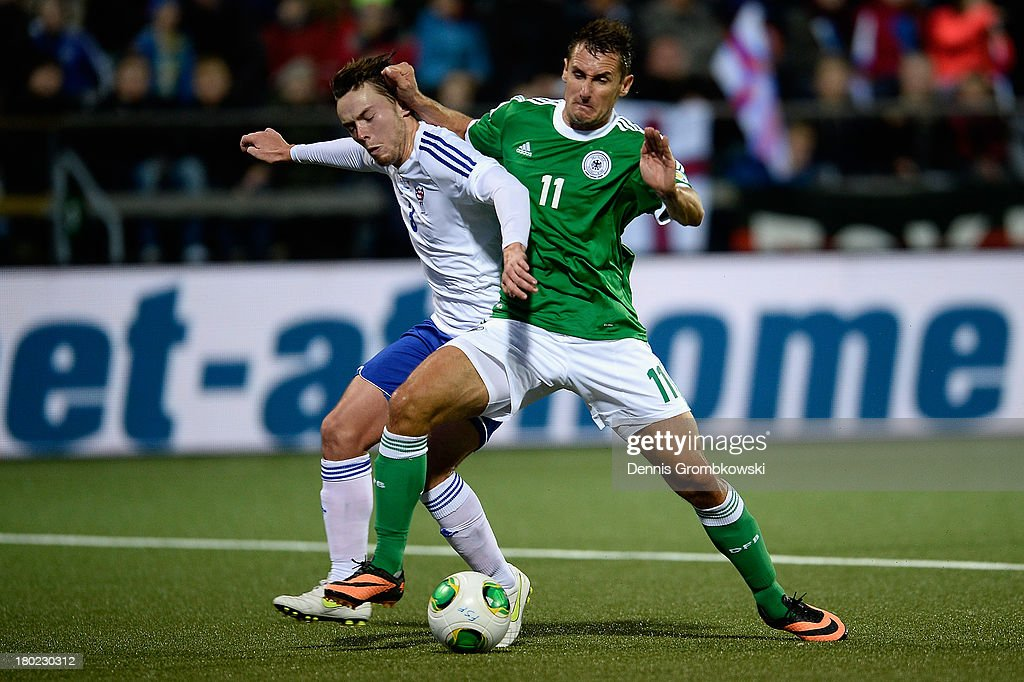 Miroslav Klose of Germany and Viljormur Davidsen of Faeroe Islands battle for the ball during the FIFA 2014 World Cup Qualifier match between Faeroe Islands and Germany on September 10, 2013 in Torshavn, Denmark.