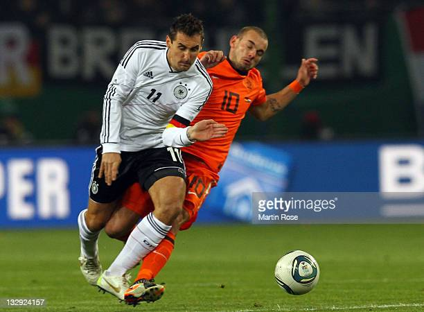 Miroslav Klose of Germany and Wesley Sneijder of Netherlands battle for the ball during the International friendly match between Germany and...