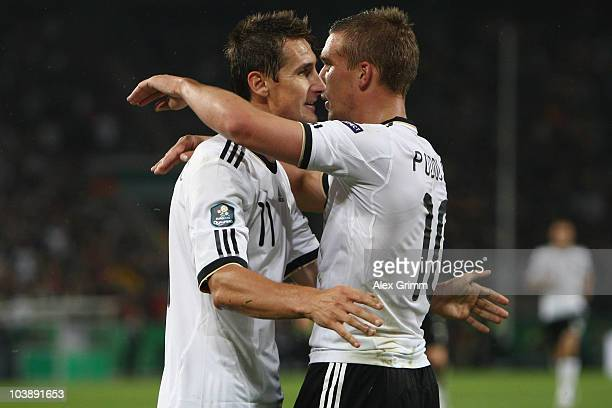 Miroslav Klose of Germany celebrates his team's third goal with team mates Lukas Podolski during the EURO 2012 Group A Qualifier match between...
