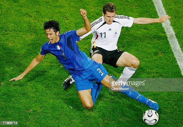 Miroslav Klose of Germany challenges Fabio Grosso of Italy during the FIFA World Cup Germany 2006 Semifinal match between Germany and Italy played at...