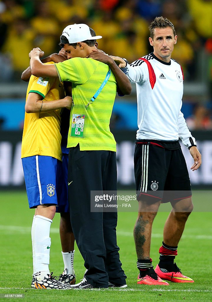 Miroslav Klose (R) of Germany consoles Thiago Silva (C) and Oscar (L) of Brazil after the 2014 FIFA World Cup Brazil Semi Final match between Brazil and Germany at Estadio Mineirao on July 8, 2014 in Belo Horizonte, Brazil.