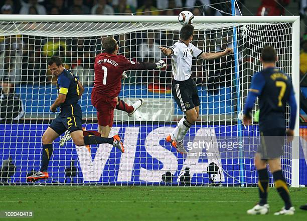 Miroslav Klose of Germany gets ahead of Mark Schwarzer of Australia and scores the second goal for Germany during the 2010 FIFA World Cup South...
