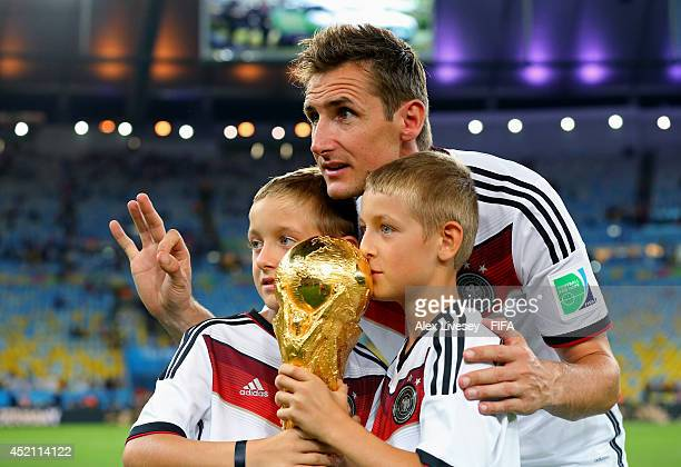 Miroslav Klose of Germany holds the World Cup trophy with his sons Luan and Noah after the 2014 FIFA World Cup Brazil Final match between Germany and...