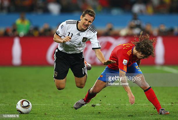 Miroslav Klose of Germany is challenged by Carles Puyol of Spain during the 2010 FIFA World Cup South Africa Semi Final match between Germany and...